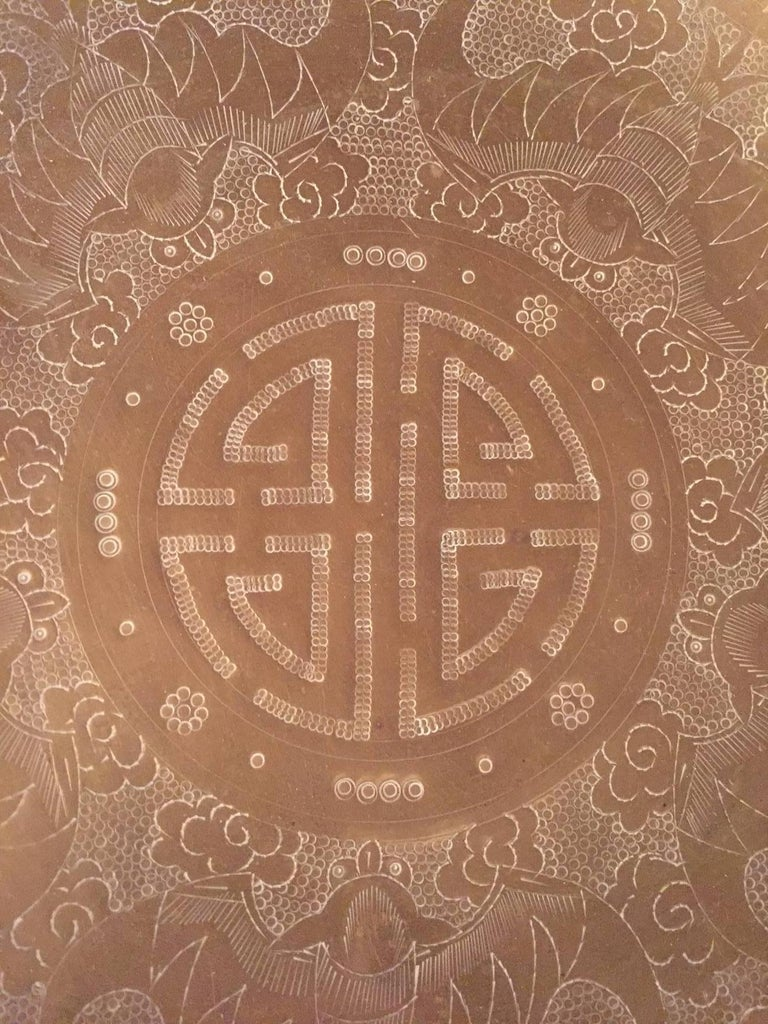 Asian brass plate with scalloped edge and embossed details.
