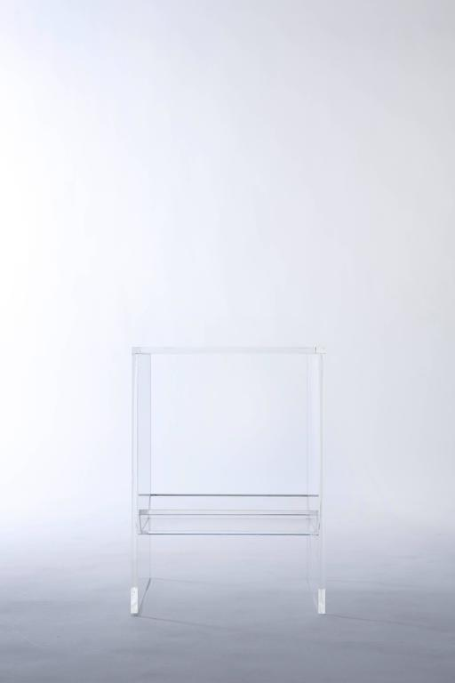 This completely transparent acrylic side table is defined by the trough nestled underneath its surface. The trough enables you to curate your own sub-seat terrarium, or to display your own accents, oddities, and other objects of intrigue.  Light