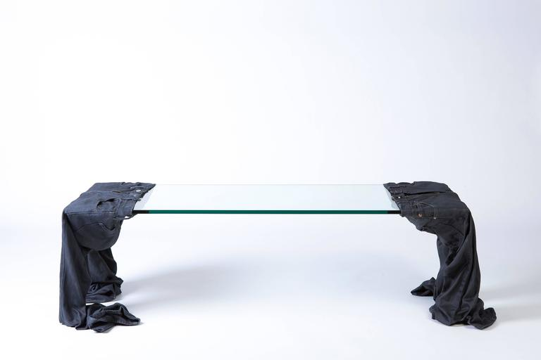 This coffee table serves as a statement piece, using recycled clothing to support a sheet of tempered glass. The two pieces are further reinforced with resin and fiberglass to give them structure, resulting in an eclectic, one-of-a-kind piece and
