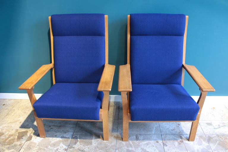 This pair of armchairs (Model GE 181 A) was designed by Hans Wegner and produced by the Danish company GETAMA. The chairs are made from oak and have just been completely reupholstered with a blue fabric.