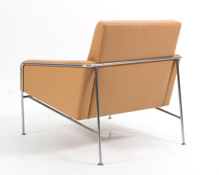 This lounge chair was designed by Arne Jacobsen and produced by Fritz Hansen. The frame is made of chromed steel, the chair has been reupholstered with beautiful natural leather in cream color. The 3300 series was originally created in 1956 for the