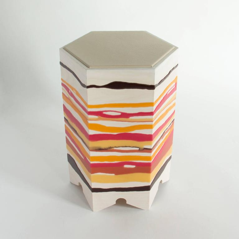 The drip or fold side table by Noble Goods is constructed of a single sheet of ash plywood that has been hand-dripped with liquid resin, then bent into a hexagonal shape. Finished with a leather upholstered top. The hot colors of this piece are