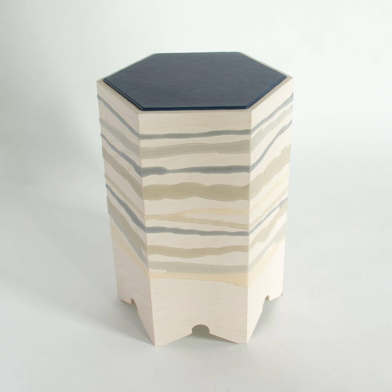 The Drip/Fold side table by Noble Goods is constructed of a single sheet of ash plywood that has been hand-dripped with liquid resin, and then bent into a hexagonal shape. Finished with a leather upholstered top. The distinct but overlapping blues
