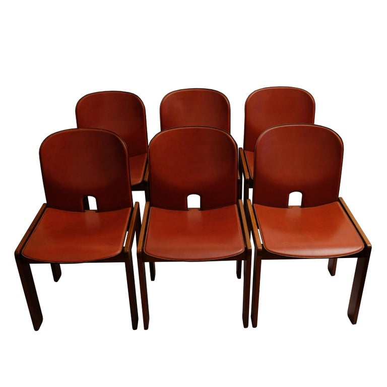 A set of six walnut and red leather chairs. The bent plywood arched back and seat upholstered with red leather and fixed on four joined walnut rectangular feet. Manufactured by Cassina. With manufacturer's labels underneath.  Literature: Domus