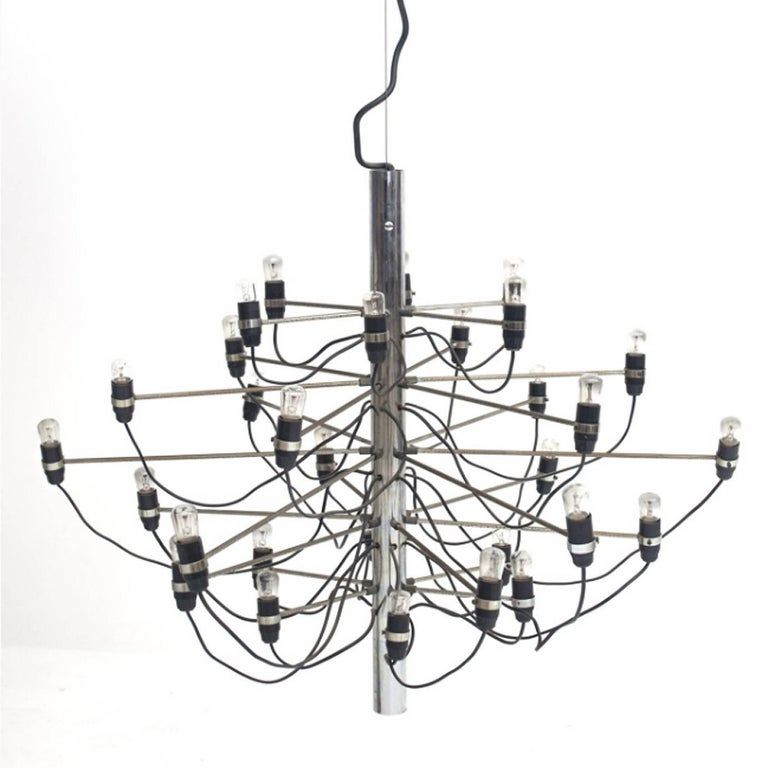 A cylinder shape plated metal chandelier, the central stem issuing thirty arms each supporting a light bulb. Manufacturer's label «AL Milano Arteluce».  Original edition.