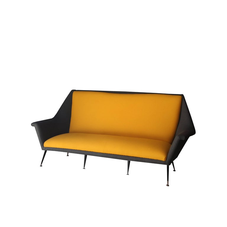 Three-seat sofa designed by Marco Zanuso with solid wood structure with lacquered legs in black finished in bronze tablets. Upholstered in two-tone wool, yellow and gray.