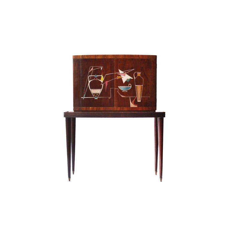 Bar cabinet composed of two bodies with solid wood structure covered in rosewood. Interior covered in mirrors, with three drawers, metal side racks and backlit on the back. Conical legs finished in brass detail.