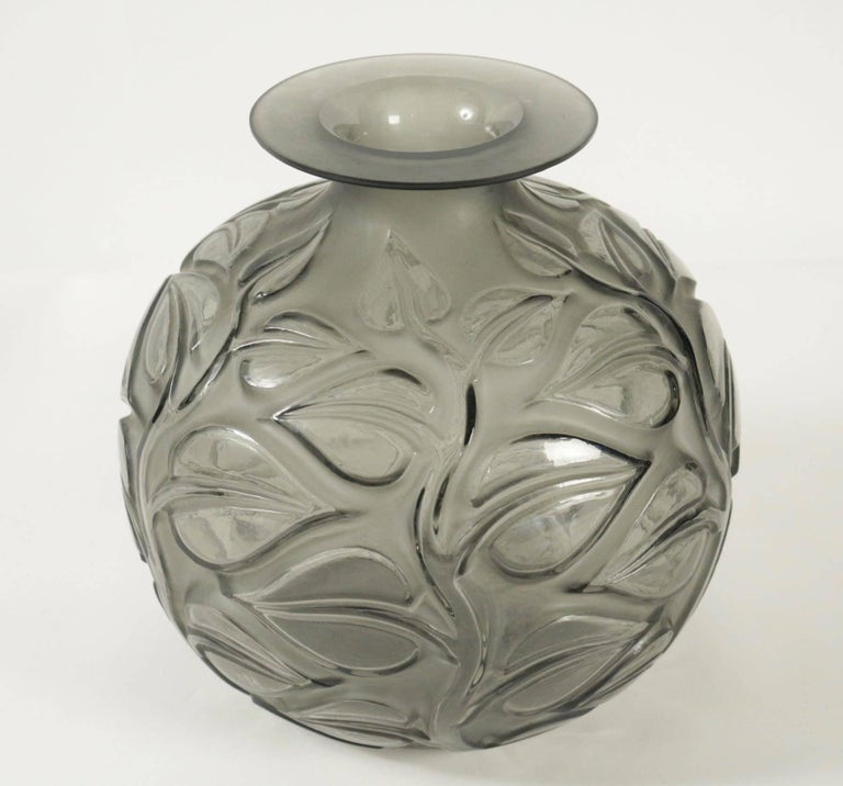 The body covered with large medium relief leaves on stems all in grey glass 26 cm tall. Frosted glass decorated with large leaves on recessed thick stems under a flat and widening rim. Sophora, model created in 1926, non repris apre's