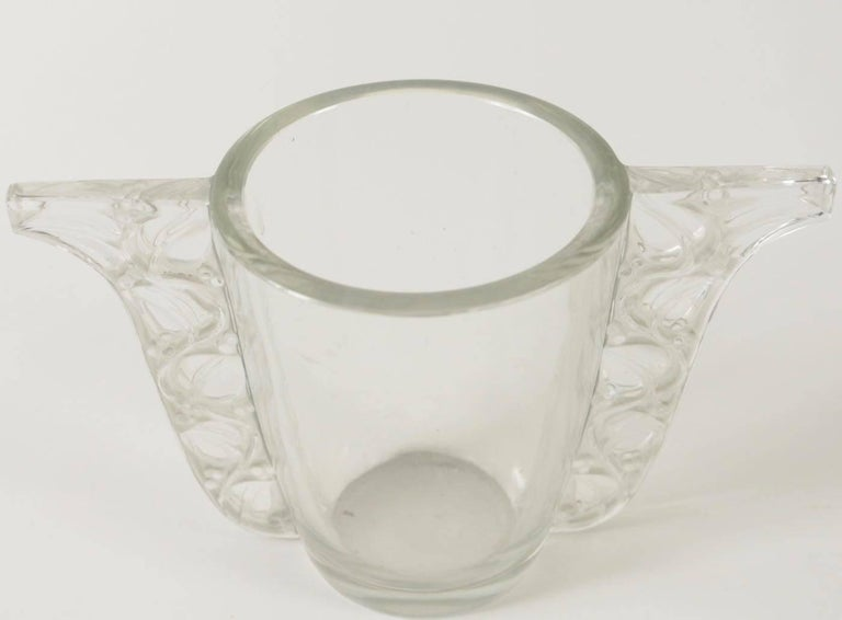 Clear glass container with a clear and frosted leaves on vines motif handle on either side