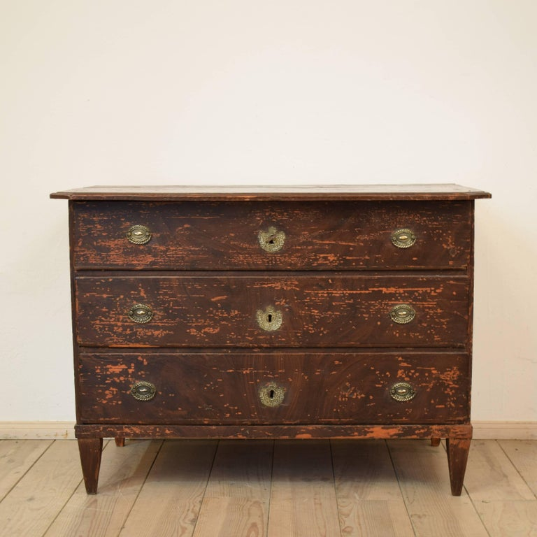 This 19th century Biedermeier chest of drawers remains a lot of the original faux wood grain painting. The commode is made circa 1800 in Germany. It has it original hardware / handles and locks.