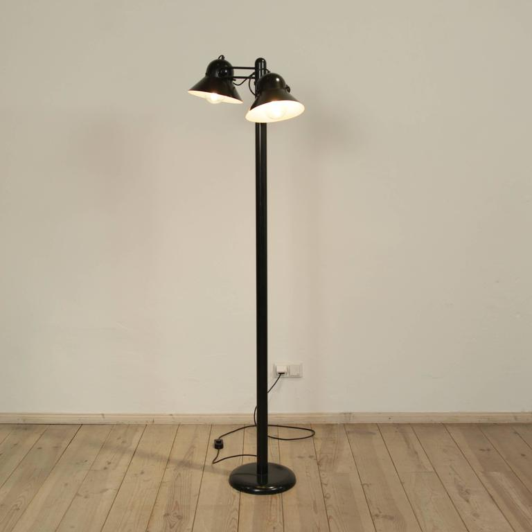 This floor lamp was produced by Stilnovo in Italy.  It is made from military green lacquered metal with two lampshades that can be adjusted and swiveled. It is a very rare piece with the two lamp shades.  The Company Stilnovo was founded in Milan by