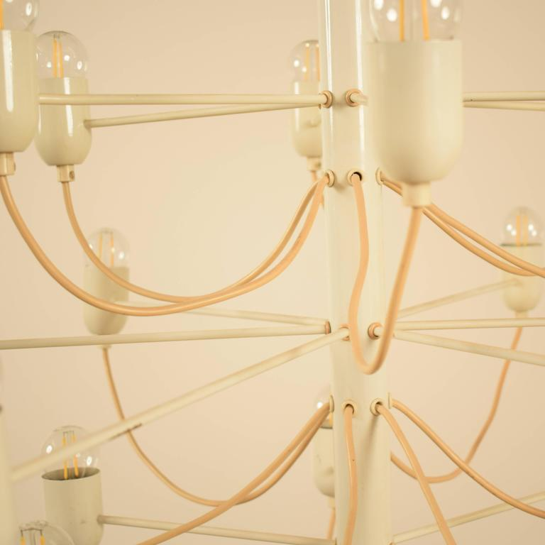 This Chandelier in the Stil of Gino Sarfatti was made in the early 1970s. It is made out of Metal and was lacquered white. The Chandelier gives a very great light and can also be lighted with LED bulbs. A great light for a modern and classical