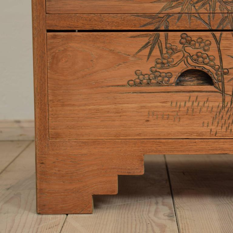 This rare colonial chest in with Asian scenes shows figures and birds in a landscape.  It is probably made in Germany, circa 1910. The commode has three drawers. The chest is from very good quality and the carvings are very well done. It has a