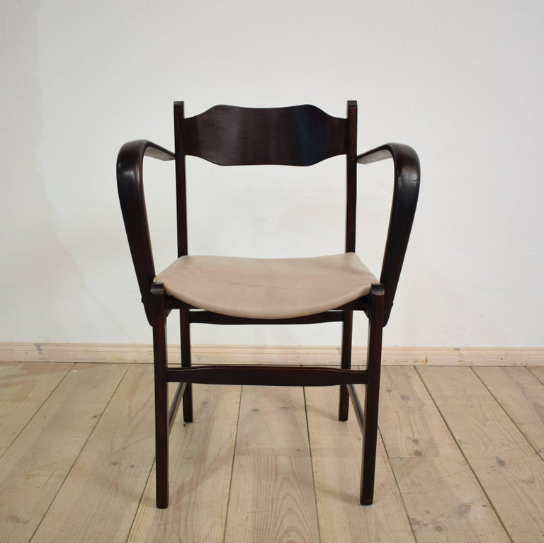 This unusual Italian Art Deco armchair is made out of beechwood. The wood is stained dark red black and the grey leather seat got new upholstered. The antique chairs is a beautiful piece of a early 1920 Italian craftsmanship. It has some really