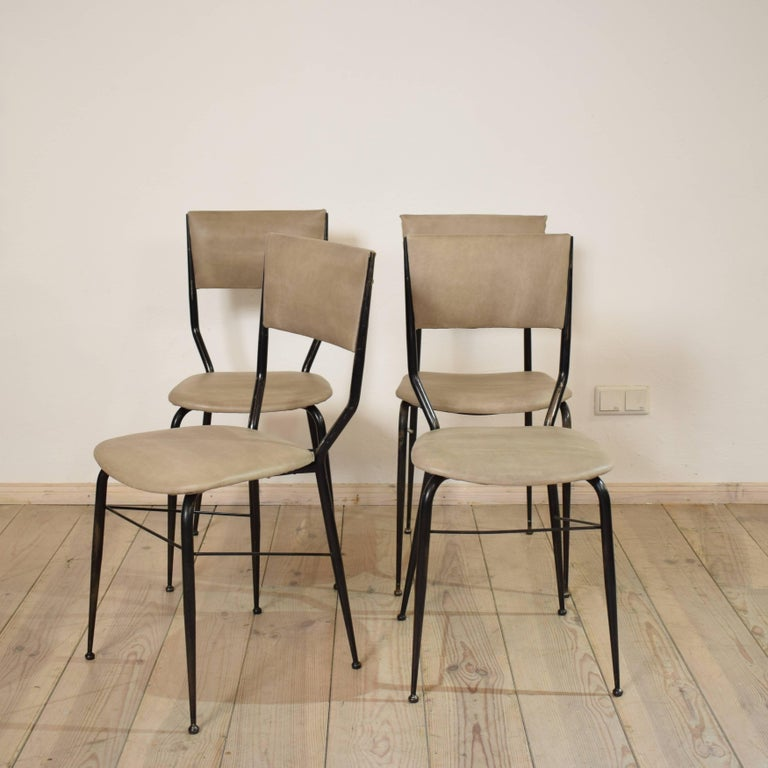 This set of four chairs from the 1950s was designed and manufactured in Italy. The chairs consist of an elegant metal frame and a padded seat and backrest. Three of the chairs are identical. One has a different backrest. The chairs have been newly