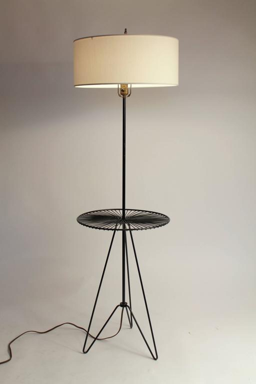 This minimalist 1950s floor lamp design is quite elegant and practical with its small table welded on the stem.   Enameled iron wire.  Well made, superb assembly, extremely sturdy.  Measures: 55 inches to finial, table is 16 inches