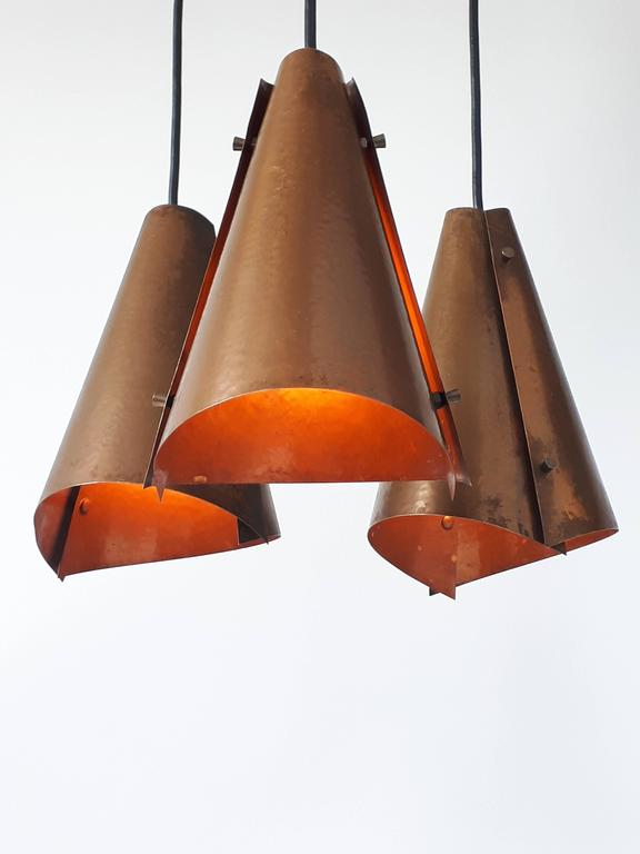 Well made hand-hammered copper pendant.   Contain three North American E26 size socket rated at 100 watts each.   Measure: 32 inches high by 14 inches wide.   Each pendant measure 10 inches high.