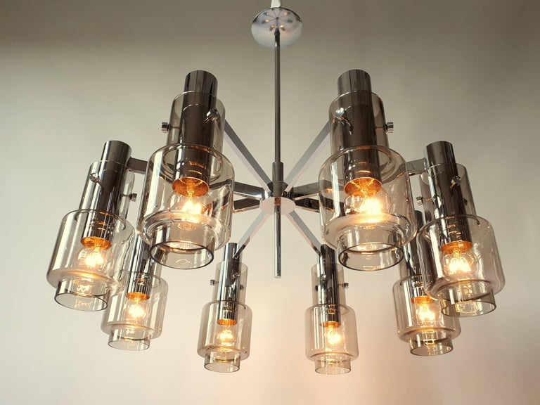 A rare  all brass chandelier coated with a thick  deep chrome finish from Hans Agne Jakobsson .   Mouth blowed smoked glass.   Prime quality material, hardware and assembly.  8 Regular North American E26 size socket .