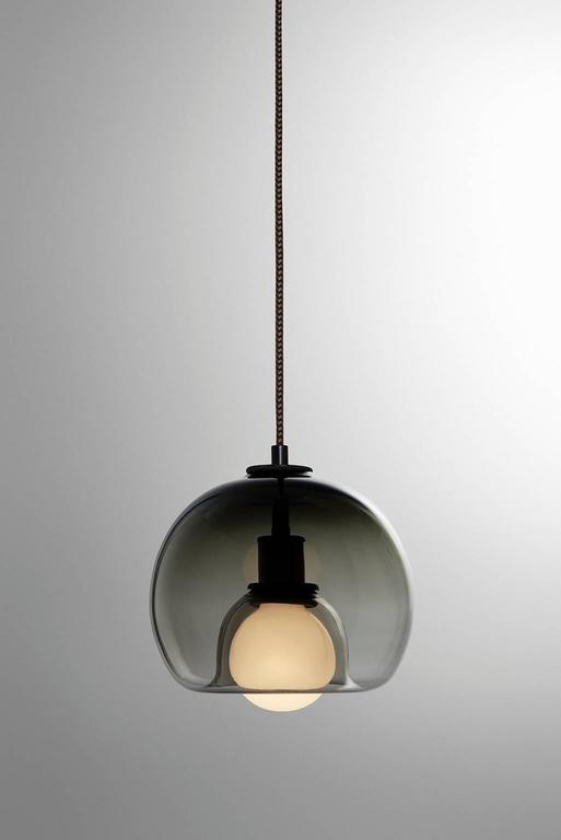 "A handblown orb gracefully inverted to house a globe bulb, like a pearl encased in a glass oyster. The Eres Smoke has an 8"" diameter with a 4' black and brown houndstooth fabric-covered cord and a 4.75"" diameter black porcelain canopy. Houses one"