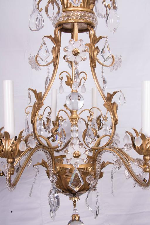 Superb Baguès crystal and gilded six-light chandelier. Decorated with crystal beads and flowers formed with faceted clear and frosted crystal. Gilt metal frame decorated with crystal beads.