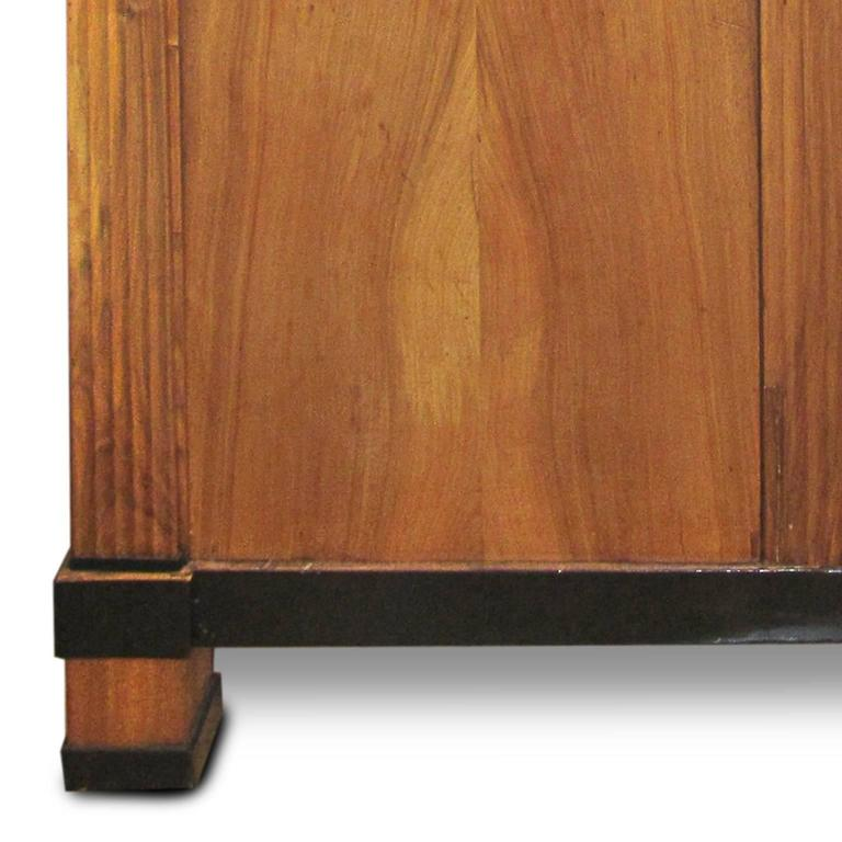 A period Biedermeier cherry and ebonized armoire with molded crown over a pair of fielded doors flanked by fluted pilasters. Doors open to a shelved interior. Raised on block feet.