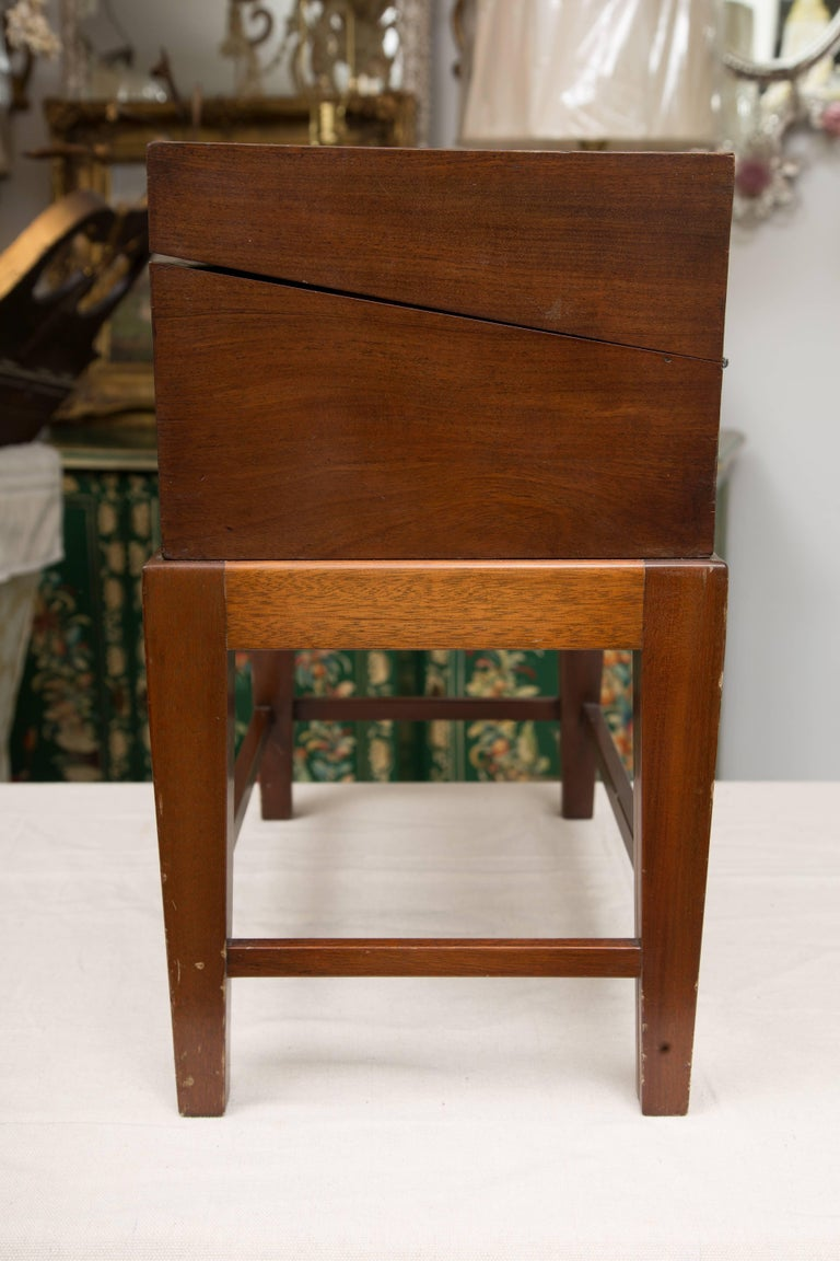 This is a traditional mahogany English mahogany with lap desk with satinwood banding, opening to reveal inkwells, interior drawers and writing surface, fitted to later stand, circa 1800 (box).