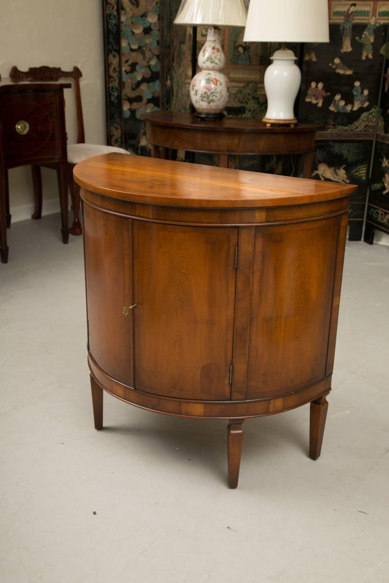 This is a quietly elegant pair of cherrywood Biedermeier style demilune side cabinets with conforming tops, having a straight edge, over a pair of cupboard doors, opening to reveal interior shelving and raised on square tapered legs 20th century.