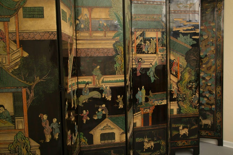 This stunning and sophisticated 12 black Coromandel screen is painted with detailed village scenes showing foliage, housing, walkways, and people -engaged in a variety of activities. The screen features a border with animals, foliage and other