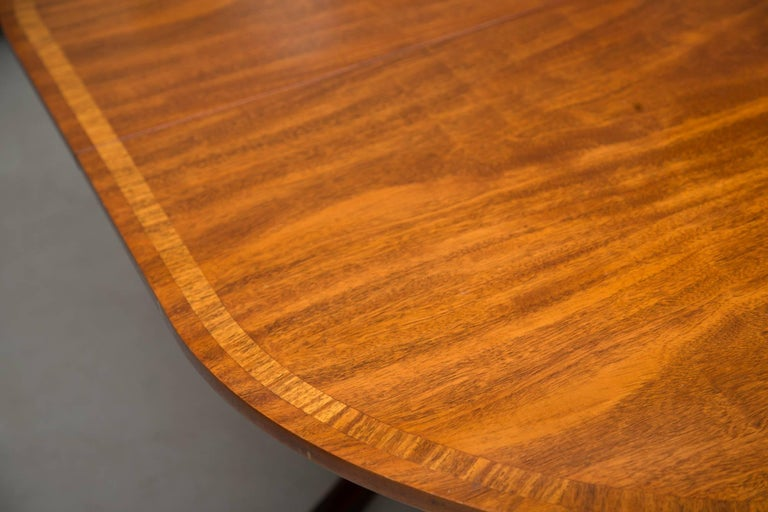 This English George III style double pedestal mahogany oval dining table has a beautifully figured mahogany top with satinwood banding. The table can be extended to 8 feet by inserting two additional leaves. The top is supported by two baluster