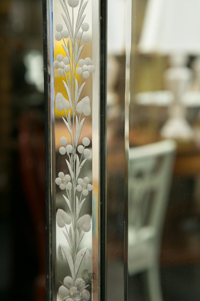 This is a Classic example of a Venetian mirror. There a shaped decorative cornice over a mirror plate surrounded by an etched mirror frame with applied glass corners, circa 1920.