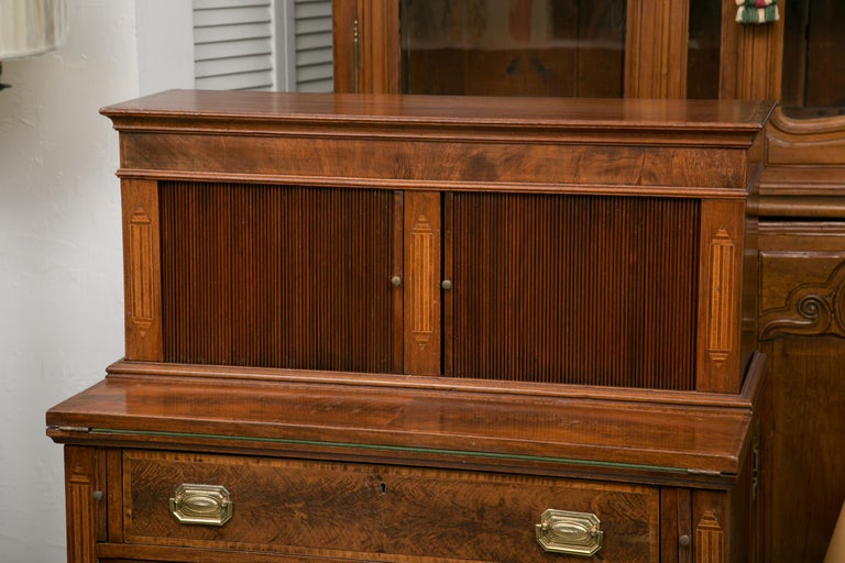This is a Classic American Federal writing desk with a tambour door on the top section when open it reveals small drawers and document compartments. The bottom section has a fold over writing section with a felt surface and two long drawers below.