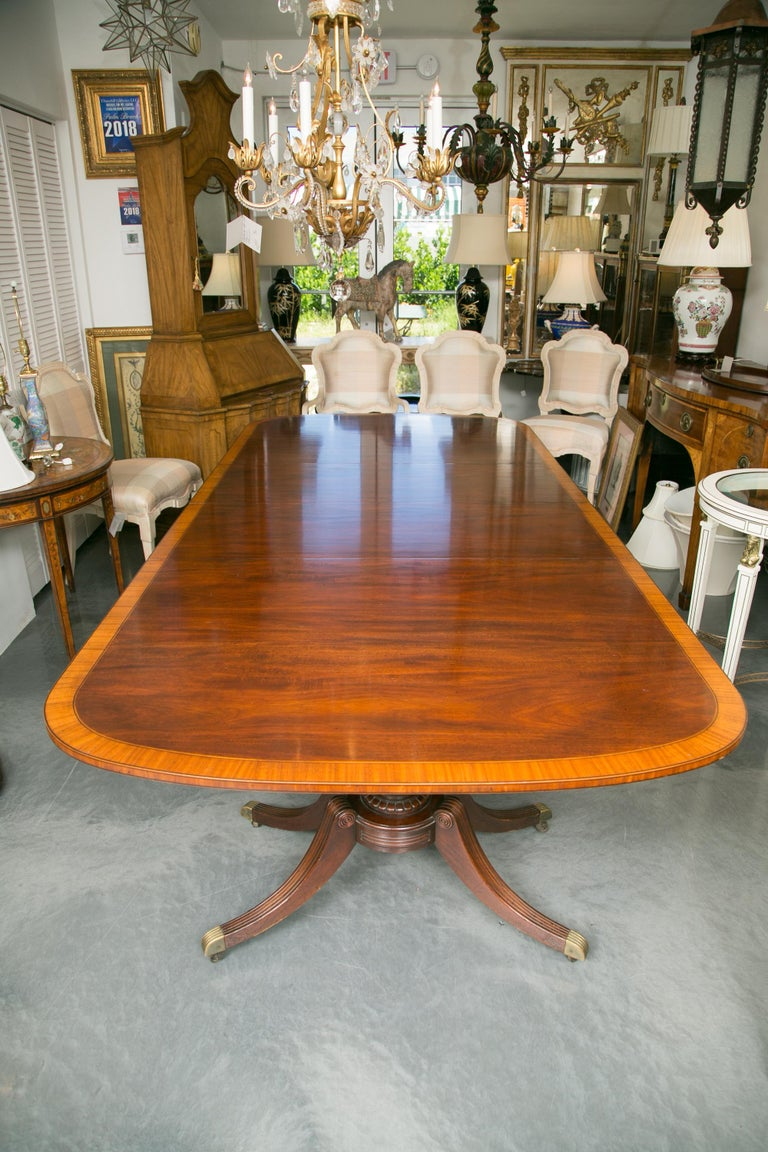 This classic English dining room table has a race-track mahogany top that is crossbanded in a wide satinwood border around the perimeter of the table as well as the edge. The top is oval and rests on a sturdy regency style baluster base with four