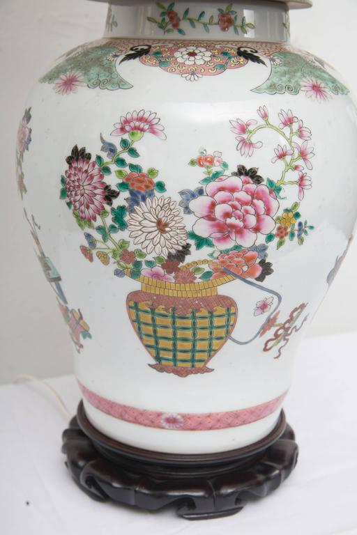 This lovely pair of Chinese lidded urns are painted with baskets and floral sprays affixed to hand carved scalloped bases, 20th century.