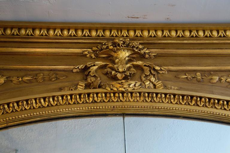 This is an unusually large French giltwood mirror with a straight egg and dart cornice over a deep frieze with a central flowering urn flanked by leafy vines above an arched mirror with a conforming carved architectural frame surrounding a central