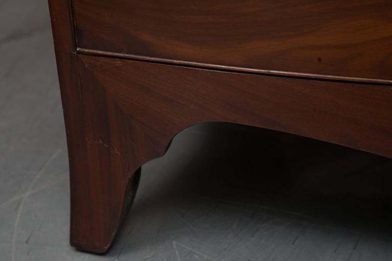 This Classic English Georgian bow front chest of drawers has a top with straight edge and brush slide over three long graduated drawers over a shaped apron, raised on splay feet, circa 1800.