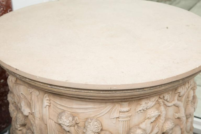 This impressive circular fountain has been assembled as a center table with later lime stone top. The item depicts classic figures in naturalistic vignettes representing various lifestyles. 20th century.