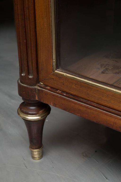 This Louis XVI style mahogany bookcase with brass accents has a Carrara marble top framed by a pierced gallery over two long glazed doors. The doors open to reveal interior shelving and is raised on round tapered feet, 19th century.