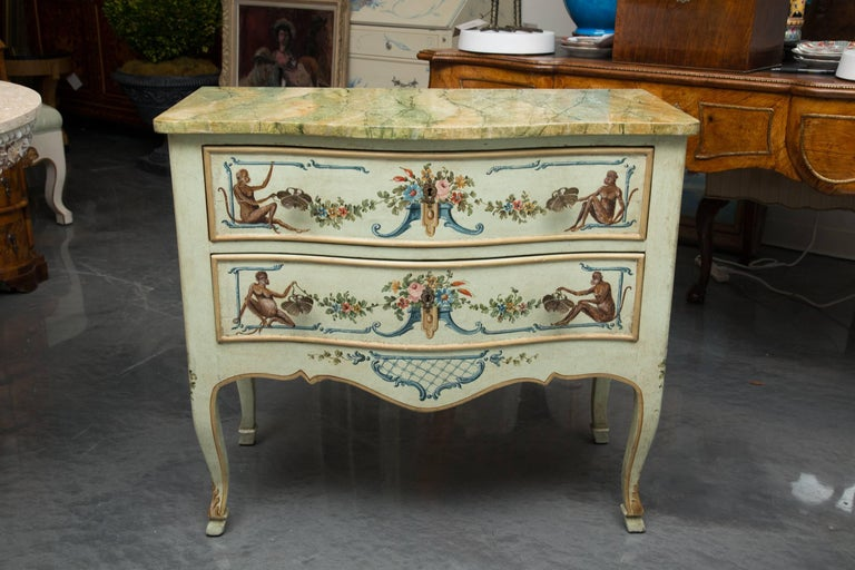 This is a whimsical, yet sophisticated Venetian commode artfully  painted with monkeys flanking floral bouquets and swags on a soft blue background. A beautiful highly glazed  faux marble top offers a realistic image of polished marble over two long