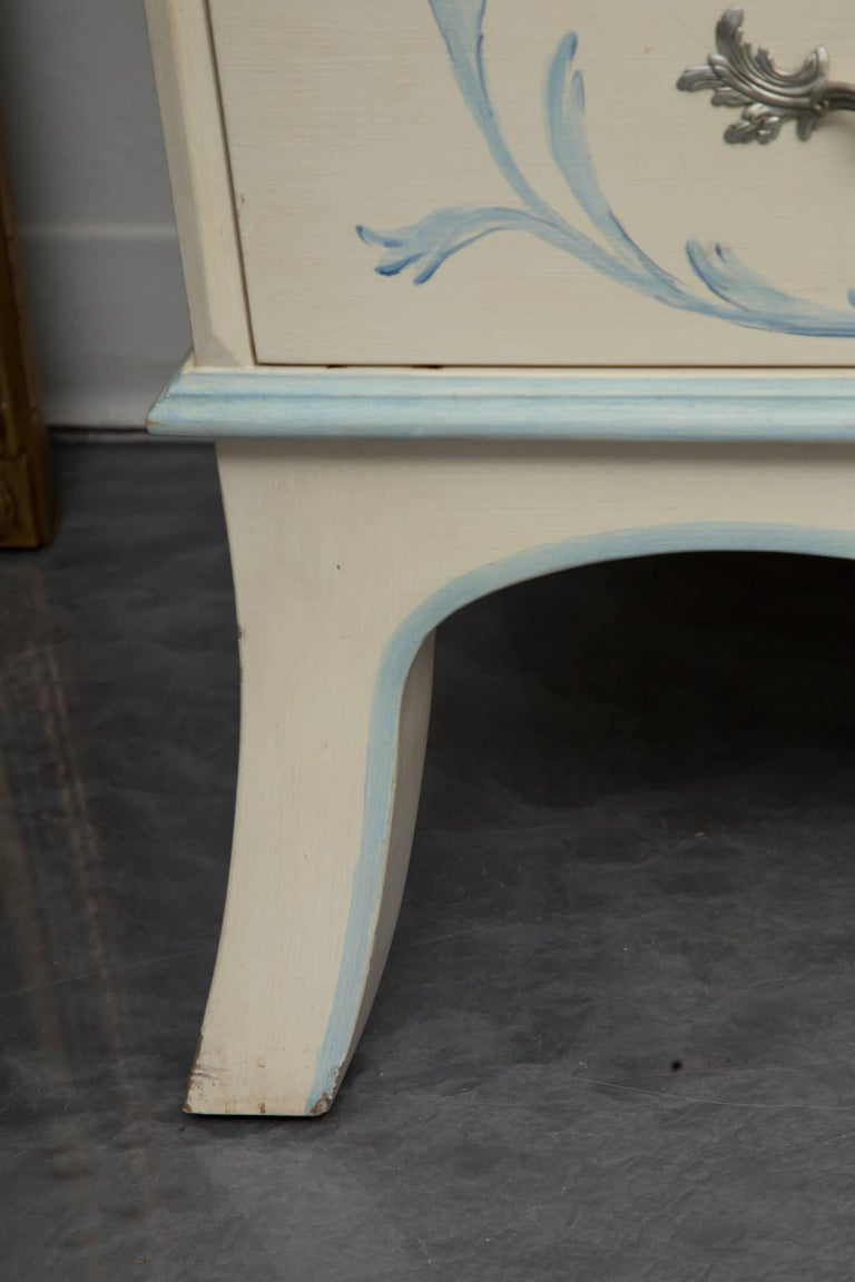 This white-painted secretary bureau bookcase is custom and has been artfully hand painted with soft, delicate blues yielding a romantic theme of flowers, baskets and trailing vines  The upper section has antiqued mirrored mullioned doors over candle