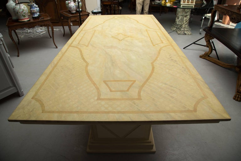 This is an elegant Italian dining table. The top is custom painted with a faux Jerusalem limestone finish, and embellished with a painted decorative ornamentation. The case piece supported by two plinths with geometric architectural moldings, 20th