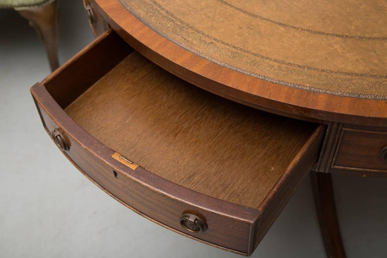 This 20th century mahogany bench-made circular drum table has a tanleather inset with gilt tooling framed by mahogany crossbanding. The wide frieze has a combination of faux and functional drawers accented with Fine beading. The circular structure