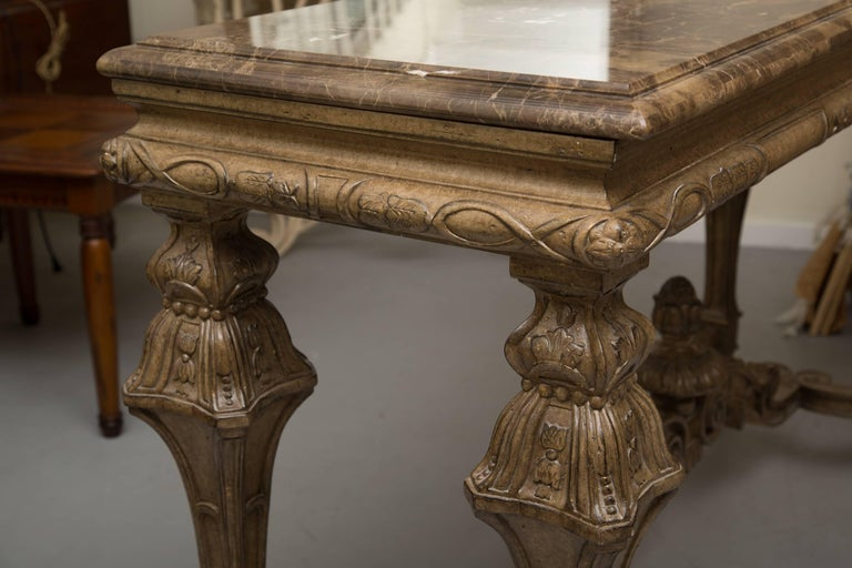 This rectangular console table can serve as a sofa table, centre table or as an impressive wall table as an anchor for any room. The marble-top rests on a deep frieze with hand-carved features typical of high style Italian Renaissance design. The