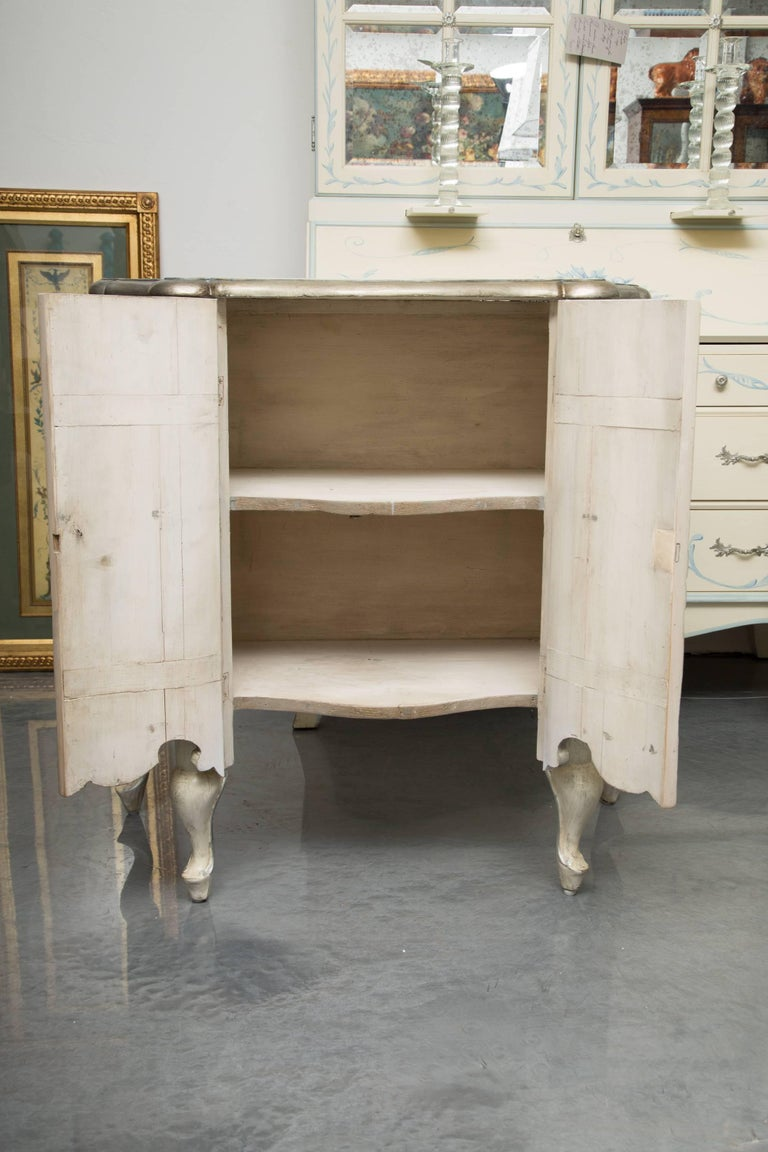 This is a sophisticated pair of blue-washed and cream-painted serpentine two-door cabinets with parcel silver highlights. The top with beveled edge is over a pair of paneled doors and inverted serpentine sides, conforming to the top. Each cabinet is