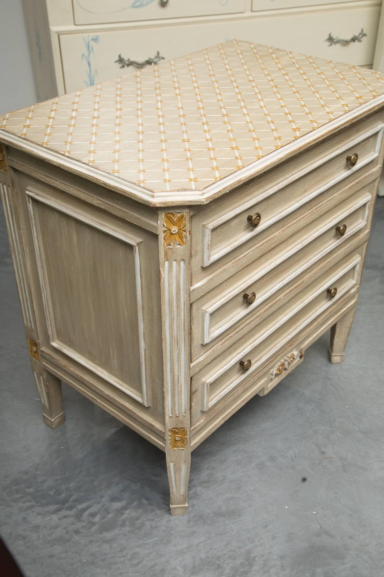 This is a stylish pair of custom gray painted and parcel-gilt chests. The top has a cross-hatch painted design over three long drawers with cream-painted moulding replicated on the sides and flanked by canted receded corners, raised on short tapered