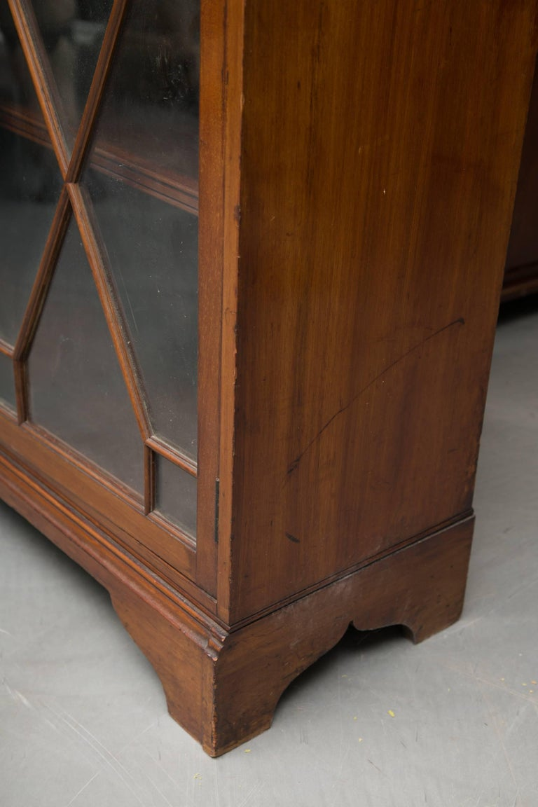 This dwarf English mahogany bookcase has a small shaped cornice above two fixed sections, top and bottom, each with a pair of geometric glazed astragal doors, raised on bracket feet, 19th century.