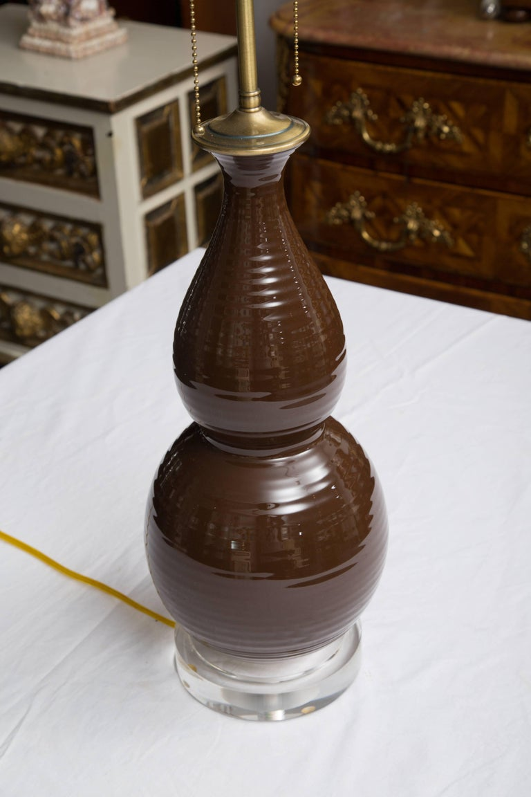 This is a pair of decorative chocolate brown double gourd table lamps with a 'ribbed' design on the gourd, The lamps are situated on circular plexiglass bases. 20th century.