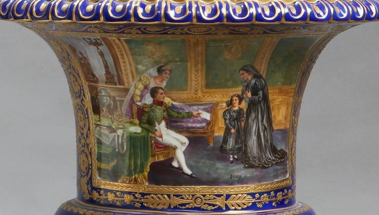 A 19th century French manufacture Impériale de Sèvres style blue urn gilt and painted with two scenes. The first painting is after a work by Frédéric Legrip entitled, 'L'Empereur Napoléon 1er donne audience à la comtesse de Bonchamps' and