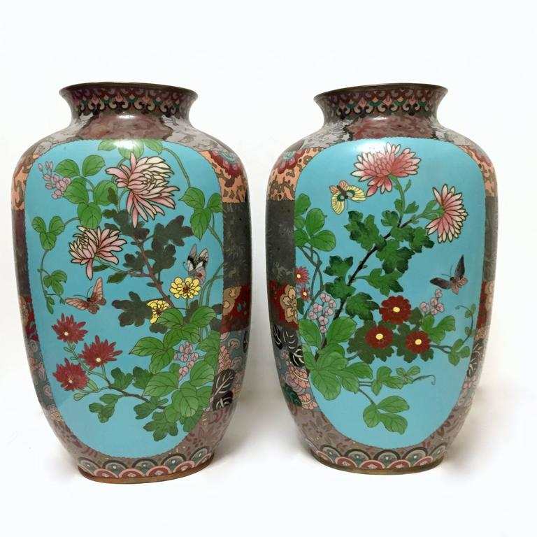 A pair of Japanese cloisonné enamel vases of slightly compressed tapering form. They are heavily ornamented on the neck, shoulders and sides with various motifs and contain central panels of a light blue background that each feature: Butterflies,