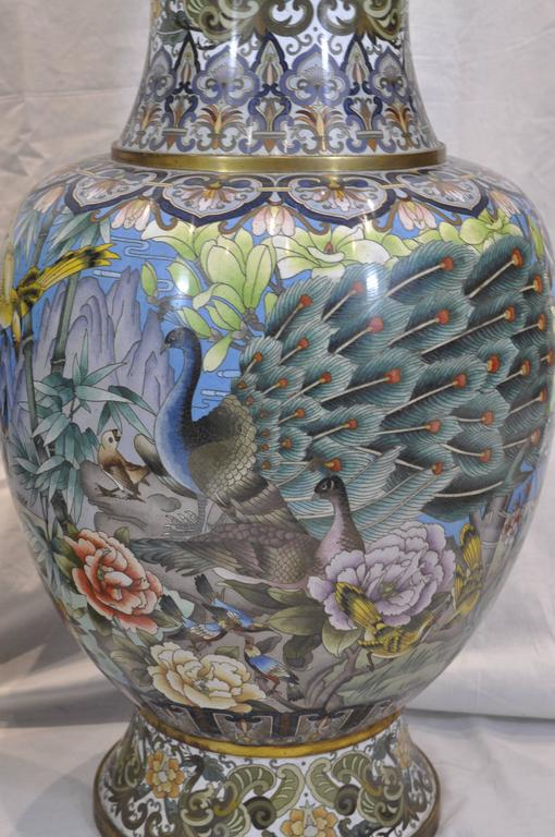 A pair of Chinese ormolu-mounted polychrome cloisonné vases decorated with a variety of birds including: roosters, peacocks, parrots, pigeons, doves and more. They also feature flowers and branches on the main body sections, whilst the neck and foot