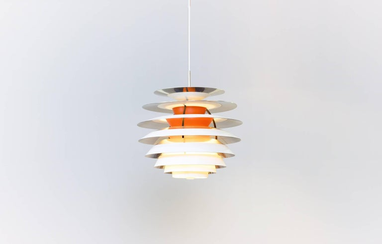Wonderful pendant lamp. Out of production. White/orange lacquered metal and chromed parts with black lacquered brass fittings. New white 2.5 m fabric cord.  Perfect original condition with minor wear consistent with age and use.